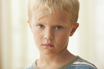 Caucasian boy with bandage on forehead