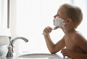 Caucasian boy pretending to shave his face