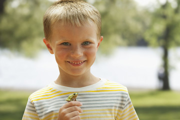 Caucasian boy holding small frog