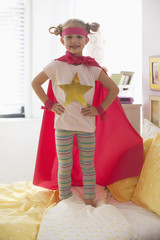 Caucasian girl dressed as superhero playing on bed