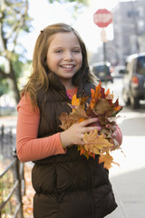 Caucasian girl holding autumn leaves
