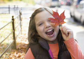 Caucasian girl holding an autumn leaf