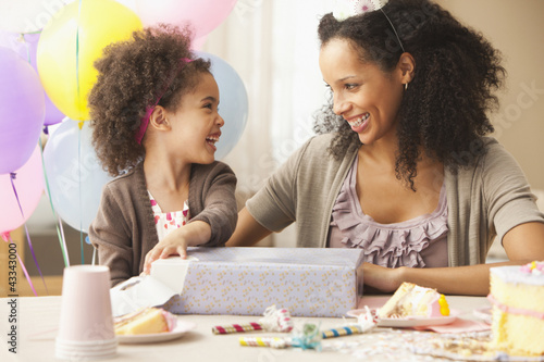 Mixed race mother watching daughter opening birthday present