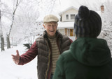 Caucasian man in snow greeting grandson