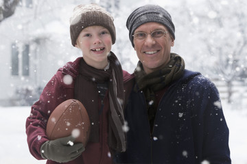 Caucasian father and son playing football in the snow