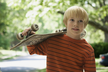 Caucasian boy carrying skateboard