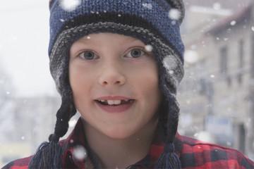 Smiling Caucasian boy standing in snow