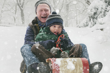 Caucasian man sledding with grandson in the snow