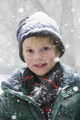 Caucasian boy standing in the snow
