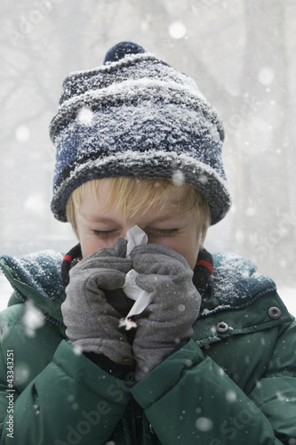 Caucasian boy blowing nose in snow
