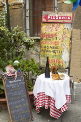 Sign and table outside pizzeria