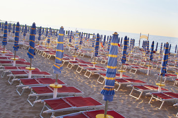 Umbrellas and beach chairs in a row on beach