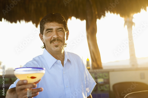 Hispanic bartender serving cocktail