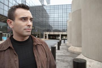 Serious Hispanic man standing in urban courtyard
