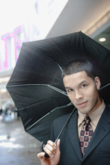Hispanic businessman holding umbrella