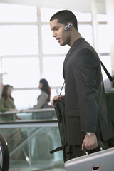 Hispanic businessman carrying suitcase and talking on hands-free cellular device