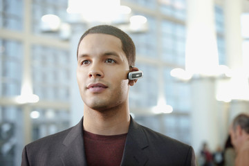 Hispanic businessman wearing hands-free cellular device