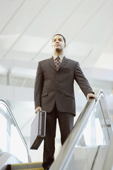 Hispanic businessman carrying briefcase on escalator