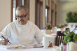 Hispanic chef working on paperwork in restaurant
