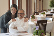Hispanic businesswoman hugging chef in restaurant