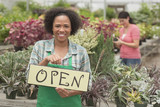 African American business owner holding hope sign in greenhouse