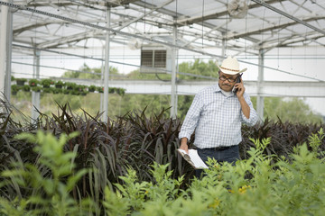 Hispanic man talking on cell phone in greenhouse