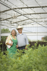 Smiling Hispanic workers standing in greenhouse