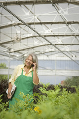 Hispanic worker talking on cell phone in greenhouse