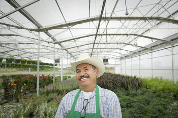 Smiling Hispanic worker standing in greenhouse