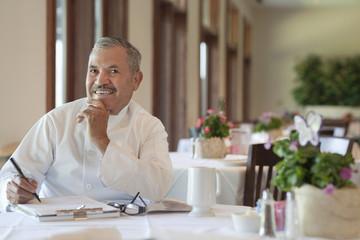 Hispanic chef working on paperwork in restaurant