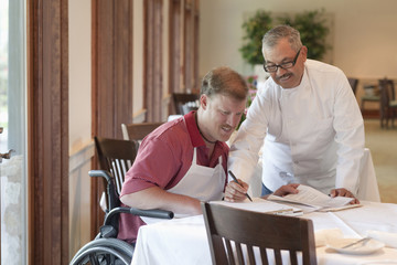 Chef going over paperwork with worker in wheelchair