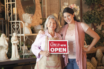 Hispanic business owners holding open sign in front of shop