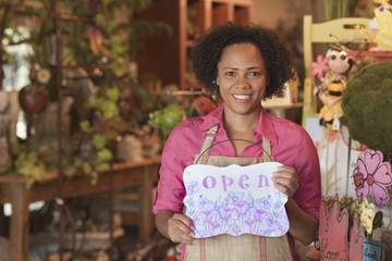 African American business owner standing in shop holding open sign