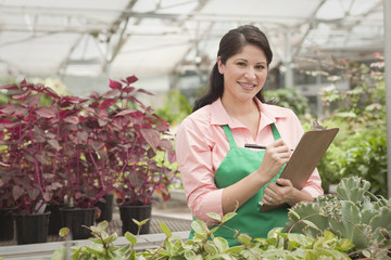 Hispanic worker writing on clipboard in greenhouse