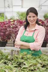 Hispanic worker standing with arms crossed in greenhouse