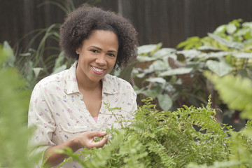 African American woman looking at plants in greenhouse