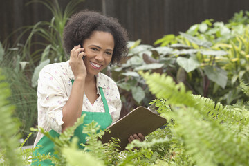 African American worker talking on cell phone in greenhouse