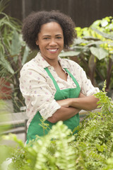 African American worker with arms crossed in greenhouse