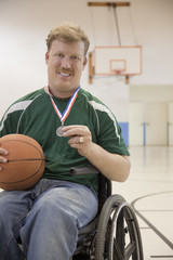 Caucasian man in wheelchair holding basketball medal