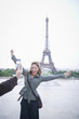 Hispanic woman posing for photograph near the Eiffel Tower