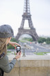 Hispanic woman taking photograph of the Eiffel Tower