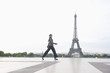 Hispanic woman walking near the Eiffel Tower