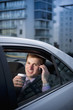 Caucasian businessman drinking coffee and talking on cell phone in car