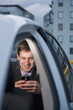 Caucasian businessman using cell phone in back seat of car
