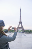 Hispanic woman taking photograph of Eiffel Tower