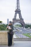 Hispanic woman looking at map near the Eiffel Tower