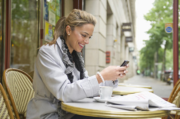 Hispanic woman using cell phone in outdoor cafe