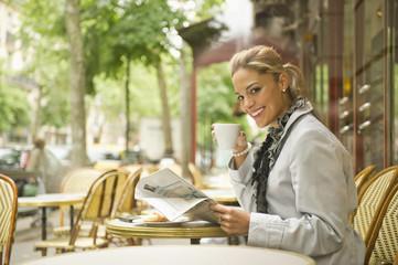 Hispanic woman drinking coffee in outdoor cafe