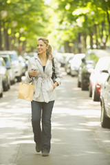 Hispanic woman walking on city street with shopping bag