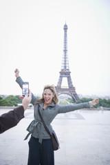 Hispanic woman posing for photograph near the Eiffel Tower